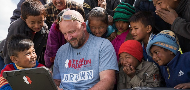 Team Rubicon member Brian Brown watches aerial footage captured by a drone as on lookers from Shermathang, Sinduhupalchok, look at his laptop joyfully.
